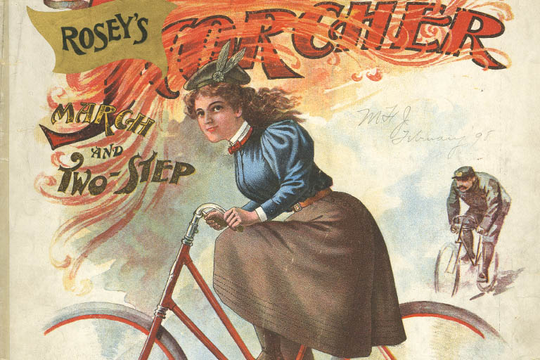 Woman riding red bicycle in the foreground, man in uniform also on bicycle in the background