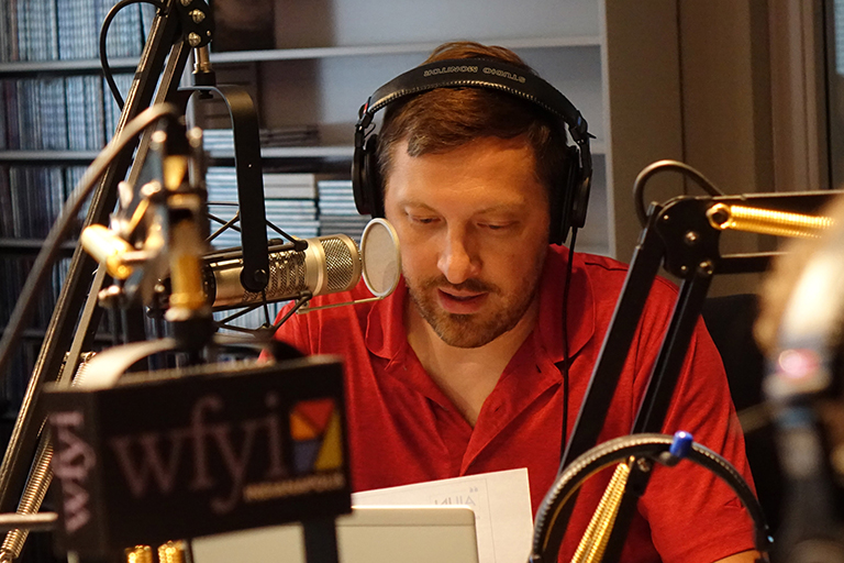 A white male with brown hair is pictured behind a microphone inside a recording studio. The letters wfyi are visible on the equipment in the foreground.