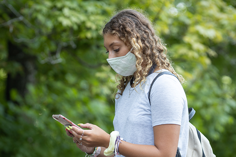 A female student uses her phone in an exterior location with visible greenery.