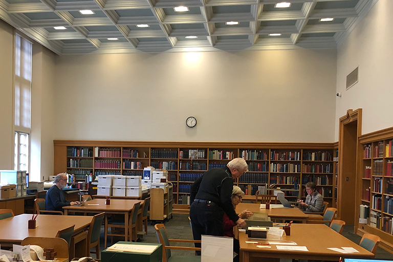 The Lilly Library reading room is pictured with tall ceilings and windows. A wall of bookshelves, several tables and a few researchers working are visible.