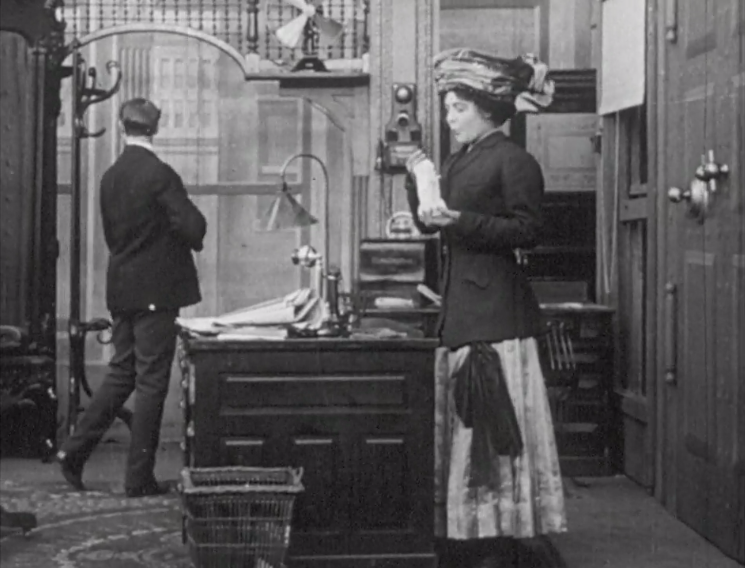 Still from silent film showing a man and a woman in late victorian dress
