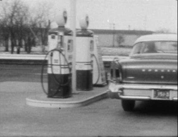 Still showing gas pumps and back of an old car