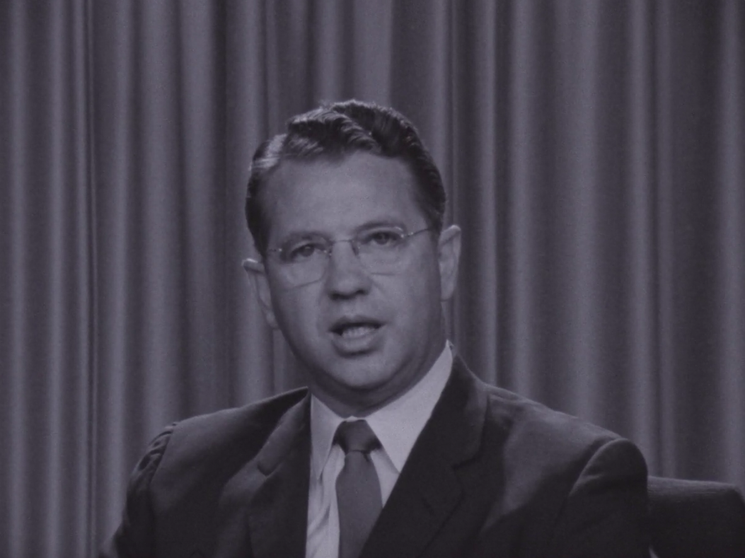 picture of senator Hartke in a suit and tie against curtained background