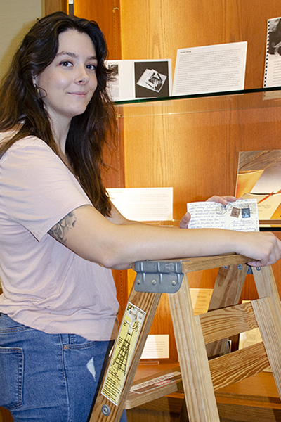 A woman pauses on a ladder to show a postcard in her hand. She is in front of a glass display case where many other papers are displayed.
