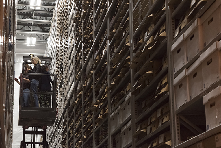 A person rides a forklift inside a warehouse holding shelves of film canisters.