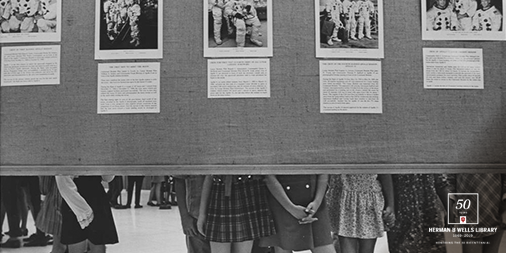 A black and white image from 1970 shows elementary students viewing an exhibit at Wells Library