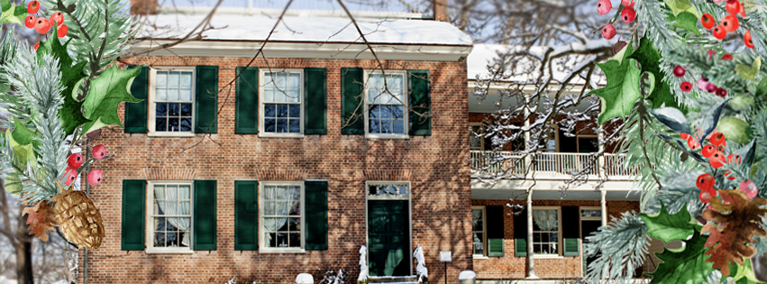 A festive frame of greenery is overlaid on a snowy photo of the Historic Wylie House in the snow