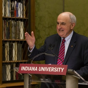 The president of Indiana University, Michael McRobbie is speaking at a podium in the Lincoln Room of the Lilly Library