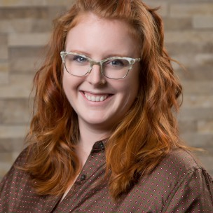 Image shows a headshot of a red-haired women wearing glasses.