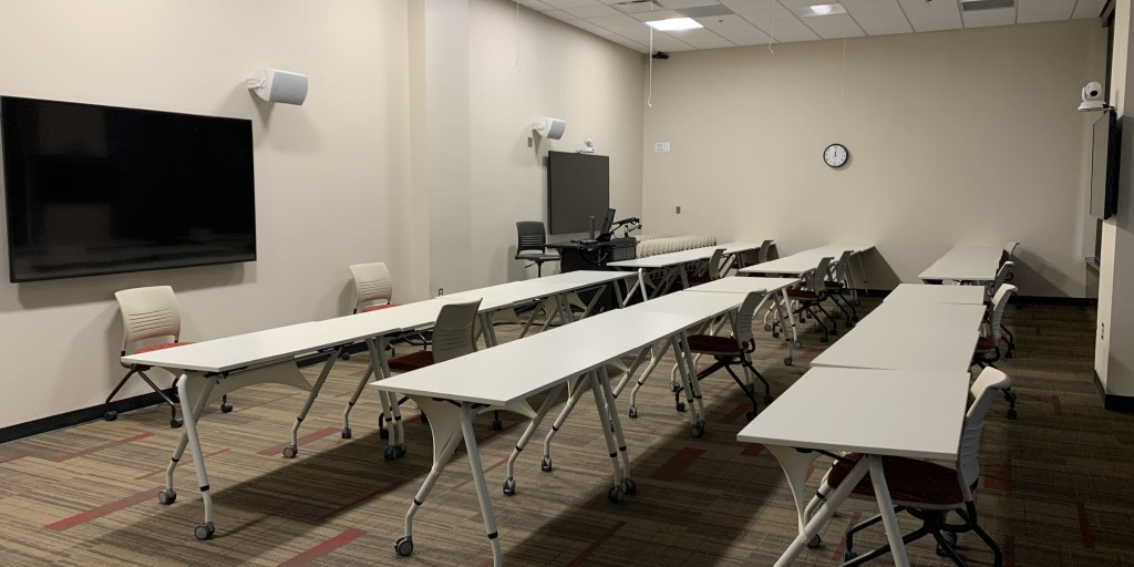 E174 meeting room with long rows of tables and two presentation screens