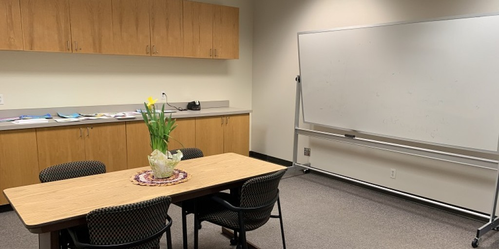 Interior of Collaboration Room showing a table with four chairs, a large whiteboard, and a countertop with cabinets above and below