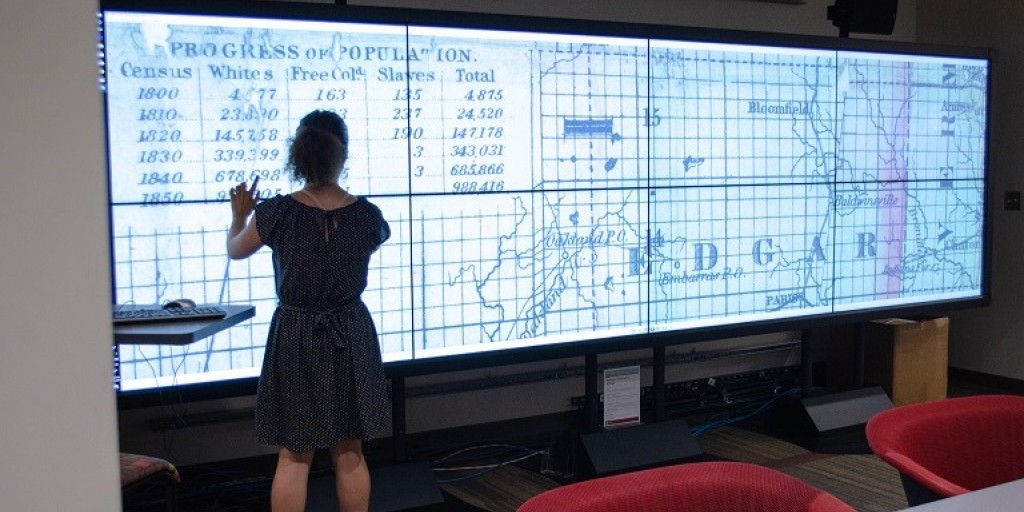 IQ-Wall displaying a historical map, with a person standing in front of it