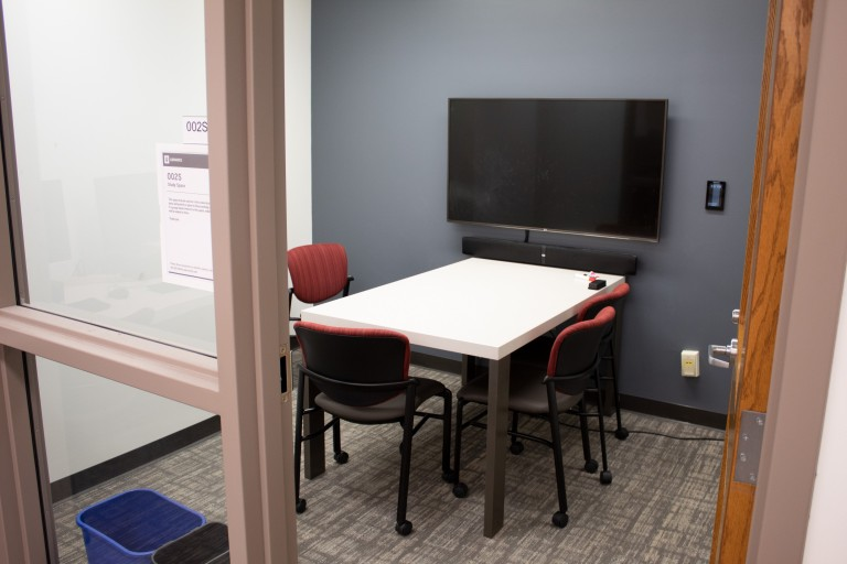Four person table and tv screen in a study room in the Science Library.