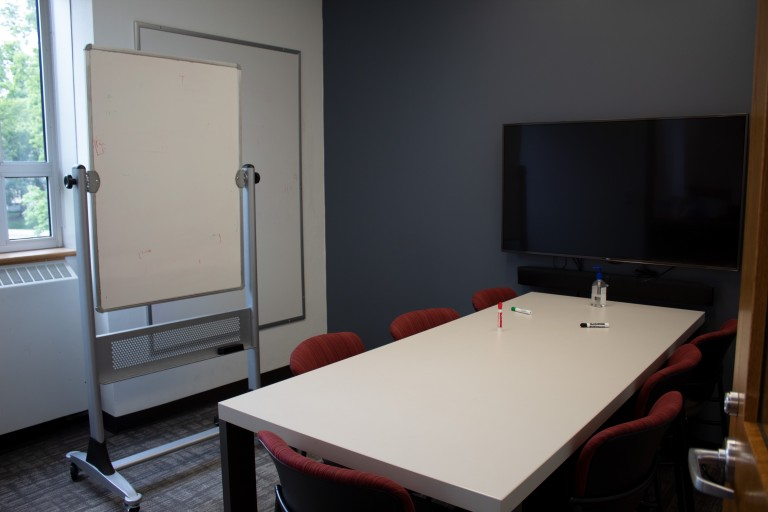 Six person table, one white board on the wall, one white board on on wheels, and a tv in a study room in the Science Library.