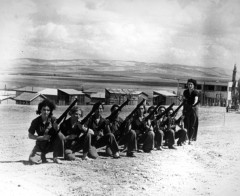 A row of women holding guns, kneeling in front of a small settlement in Palestine