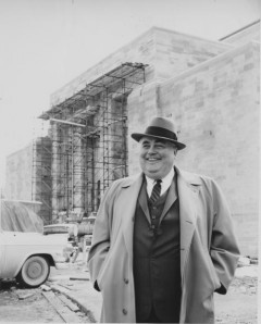 Photograph of Herman B Wells with a building under construction in the background