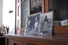 Two black and white photographs with protective coverings are displayed on a fireplace mantel.