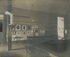 A vintage photograph depicts a university classroom with framed art on the wall.