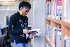 A woman in a black sweater and bold earrings browses a bookshelf in the library