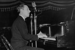 Hoagy Carmichael singing and playing a piano on a stage.