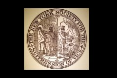 "Engraved seal reading ""The New York Society for the Suppression of Vice"" with image of man being jailed and image of man burning books"