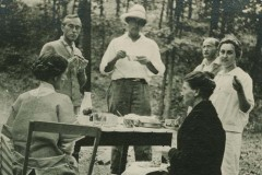Black and white image of three women and three men eating outdoors at a camp table with woods in the background. Two of the women are seated on camp chairs.