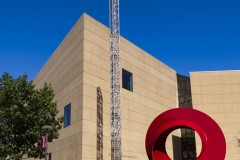 View of the Eskenazi Museum of Art in Bloomington, Indiana. A red circular sculpture and light tower occupy the foreground.