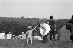 A black and white photo of the back of a toddler wearing no clothing. He reaches up to a women with a flower headband.  The image was taken at Woodstock 50 years ago.