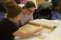 two young women are studying a rare newsprint magazine in a library