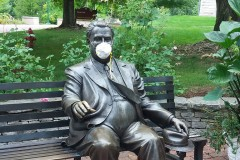 A photo of the seated statue of Herman B Wells, wearing a mask