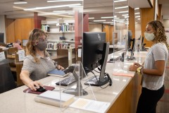 At a library, a masked staff member speaks with a student while checking out books.