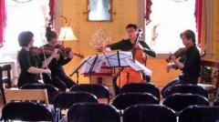 Young string quartet musicians, seated and performing with instruments in parlor of museum