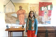 A woman, Laura Post, stands in front of her murals depicting two Wylie House historical figures.