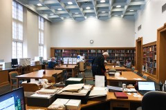 An interior view of the Lilly Library Read Room with a few patrons using materials on tables.