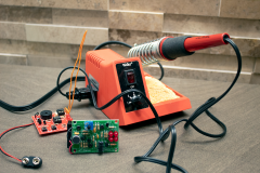 Image of an orange and red soldering iron on a table inside the Maker's Space at Herman B Wells Library