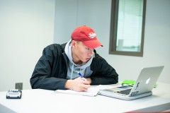 A male student wearing a red hat is taking notes while looking at a laptop