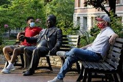 Two men wearing masks sit on park benches on a college campus.