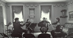 black and white, two string musicians seated, one playing violin and one playing cello