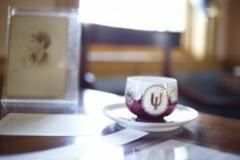 A colorful teacup with a gold Indiana University trident sits in a saucer on a table