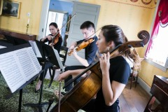 three young string musicians playing instruments (2 violins and one cello)