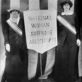 Two women standing next to a banner that says, National Woman Suffrage Association