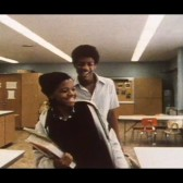 A young African American couple stands in a home economics classroom. They are both laughing. The young woman is holding textbooks and is wearing a hat.