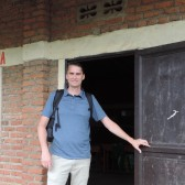 Photo of Mike Courtney, Outreach and Engagement Librarian, in front of a door in Rwanda.
